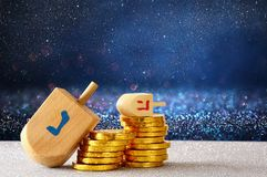 Image of jewish holiday Hanukkah with wooden dreidel. & x28;spinning top& x29; and chocolate coins on the glitter background