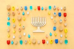 Image of jewish holiday Hanukkah with wooden dreidels colection & x28;spinning top& x29; over pastel yellow background. stock images