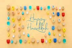 Image of jewish holiday Hanukkah with wooden dreidels colection & x28;spinning top& x29; over pastel yellow background. Image of jewish holiday Hanukkah with stock photo