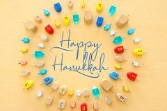Image of jewish holiday Hanukkah with wooden dreidels colection & x28;spinning top& x29; over pastel yellow background. Image of jewish holiday Hanukkah with royalty free stock photo