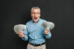 Image of joyful adult man 60s with gray hair holding money two f. Ans of 100 dollar bills and screaming in happiness isolated over black background Royalty Free Stock Image
