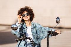 Image of joyful curly woman in sunglasses sitting on motorbike Stock Images