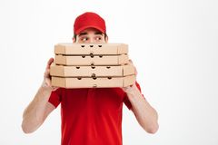 Image of joyful delivery man in red uniform covering face with s. Tack of pizza boxes and looking aside  over white background Stock Image