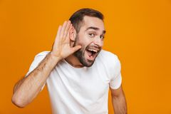 Image of joyful man 30s trying to hear something while keeping hand at his ear,  over yellow background. Image of joyful man 30s trying to hear something while royalty free stock photography