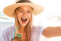 Image of joyful pretty woman 20s in summer straw hat laughing, a. Image of joyful pretty woman 20s in summer straw hat laughing and holding cocktail while taking Royalty Free Stock Image