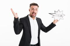 Image of joyful successful man wearing black jacket rejoicing an. D holding speech bubble with word idea in hand isolated over white background Royalty Free Stock Photo