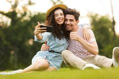 Image of man and woman 20s sitting on green grass in park and taking selfie on smartphone stock photography