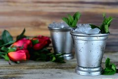 Image for Kentucky Derby in May showing two silver mint julep cups with crushed ice and fresh mint in a rustic setting. With red roses royalty free stock photos