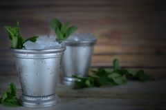 Image for Kentucky Derby in May showing two silver mint julep cups with crushed ice and fresh mint in a rustic setting. Vignette added. Copy space royalty free stock photo