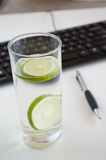 Image of keyboard, pen and glass of water at workplace Stock Photography