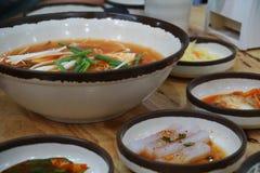 Close up Korea kimji soup with soft tofu and enoki mushroom. Korea cuisine, hot soup serve with pickle vegetable side dish. Image of Korea kimji soup with soft royalty free stock photos