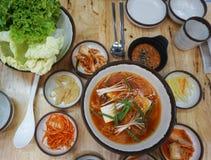 Top view of Korea kimji soup with soft tofu and enoki mushroom. Korea cuisine, hot soup serve with pickle vegetable side dish. Image of Korea kimji soup with stock photo