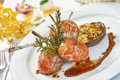 Image of lamb chops on a bed of vegetables Eggplant stuffed with vegetables. Decorated table romantic dinner Royalty Free Stock Photo