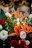 An image of a large vase of Wedding flowers with candle in a church Royalty Free Stock Photo