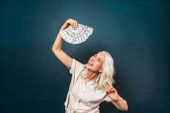 Laughing mature old woman holding money in hands. Image of laughing mature old woman isolated over dark blue background. Looking aside holding money in hands Royalty Free Stock Photo