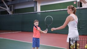 Image of lesson at indoor court with professional equipment. Child learning process of correct using a racket. Boy stock video footage