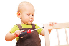 Image of little boy fixing chair with screwdriver Royalty Free Stock Photography