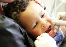 Little boy having his teeth examined at the dentist stock photo