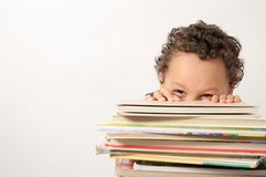 Little boy with a pile of books. Image of a little boy with a pile of books Royalty Free Stock Images