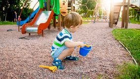 Image of little boy sitting on the playground and puring sand with small plastic spade in colorful bucket. Kid digging. Image of little boy sitting on playground royalty free stock photo