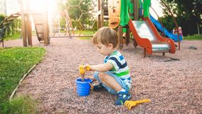 Image of little boy sitting on the playground and puring sand with small plastic spade in colorful bucket. Kid digging. Image of little boy sitting on playground stock photo