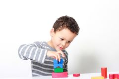 Little boy testing his creativity by building towers with toy building blocks. Image of little boy testing his creativity by building towers with toy building royalty free stock photo