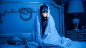 Photo of little girl covering under blanket holding flashlight in dark room. Image of little girl covering under blanket holding flashlight in dark room Royalty Free Stock Images