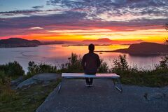 A Lone Man Sitting on A Bench Overlooking Islands and Ocean at Dramatic Sunset