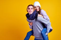 Image of lovely couple having fun while man piggybacking his girlfriend on yellow background royalty free stock photos