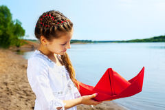 Image of lovely girl with red paper boat Stock Photo