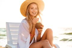 Image of lovely smiling woman 20s in straw hat drinking exotic c. Ocktail while sunbathing in deck chair on beach during summer sunrise Royalty Free Stock Images