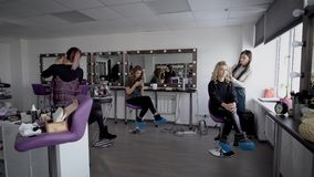 Image of luxury beauty parlour. Three models are sitting in the hall and two professional experts are working together stock footage
