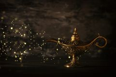 Image of magical mysterious aladdin lamp with glitter sparkle lights over black background. Lamp of wishes. Image of magical mysterious aladdin lamp with stock photography