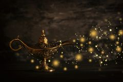 Image of magical mysterious aladdin lamp with glitter sparkle lights over black background. Lamp of wishes. Image of magical mysterious aladdin lamp with royalty free stock photos