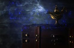 Image of magical mysterious aladdin lamp with glitter sparkle smoke over black background. Lamp of wishes. Image of magical mysterious aladdin lamp with glitter stock photo