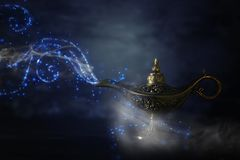 Image of magical mysterious aladdin lamp with glitter sparkle smoke over black background. Lamp of wishes. Image of magical mysterious aladdin lamp with glitter stock image