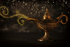 Image of magical mysterious aladdin lamp with glitter sparkle smoke over black background. Lamp of wishes. Image of magical mysterious aladdin lamp with glitter royalty free stock photo