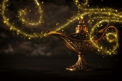 Image of magical mysterious aladdin lamp with glitter sparkle smoke over black background. Lamp of wishes. Image of magical mysterious aladdin lamp with glitter royalty free stock photos