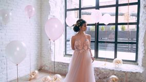 Image of the majestic Greek goddess in a spring light wonderful dress, posing surrounded by balloons, pink tones on. Video, a modest brunette with a gentle stock footage