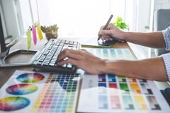 Image of male creative graphic designer working on color selection and drawing on graphics tablet at workplace with work tools and royalty free stock photo