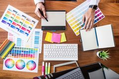 Image of male creative graphic designer working on color selection and drawing on graphics tablet at workplace with work tools and stock photo
