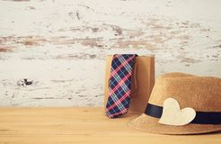 Image of male fedora hat and shopping bag with tie over wooden table. . Father`s day concept. Image of male fedora hat and shopping bag with tie over wooden Stock Photos