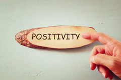 Image of male hand pointing at wooden sign with the word positivity Royalty Free Stock Images