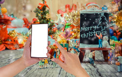 Image of male hand using phone and Christmas ornaments. On wood background Stock Images