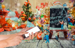 Image of male hand using phone and Christmas ornaments. On wood background Stock Photos