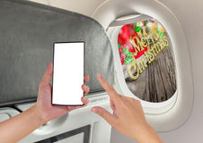 Image of male hand using phone on the plane and Christmas orname. Nts on wood background Royalty Free Stock Photo