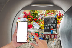 Image of male hand using phone on the plane and Christmas ornaments Stock Photos