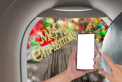 Image of male hand using phone on the plane and Christmas ornaments. On wood background Royalty Free Stock Photos