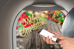 Image of male hand using phone on the plane and Christmas ornaments. On wood background Royalty Free Stock Photography