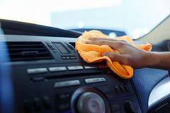 Image of male`s hand with orange rag washing car interior. Close-up stock photography